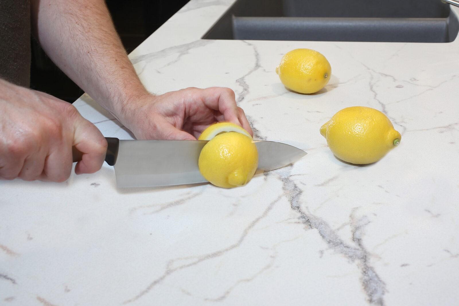 person slicing lemons on granite countertop