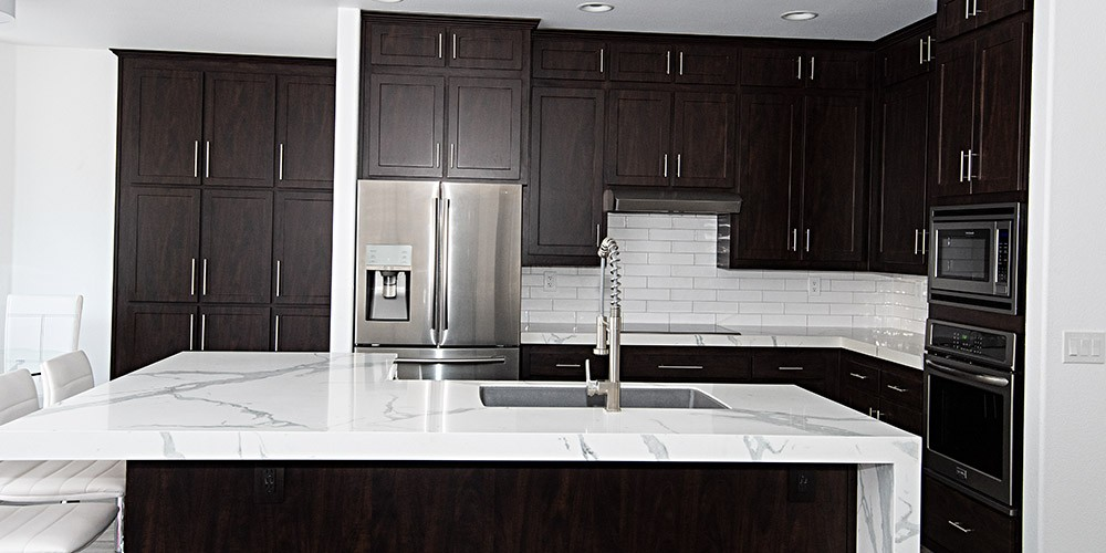kitchen after remodeling with marble countertops and dark wood cabinets