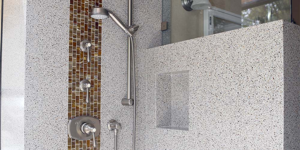 shower remodeled by Granite Transformations using granite slabs and mosaic tiles