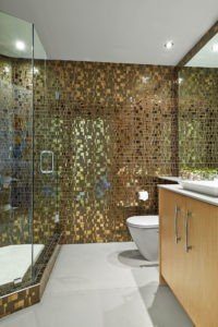 Liberty Bronzite Mosaic Tiles cover the walls and shower of this guest bathroom