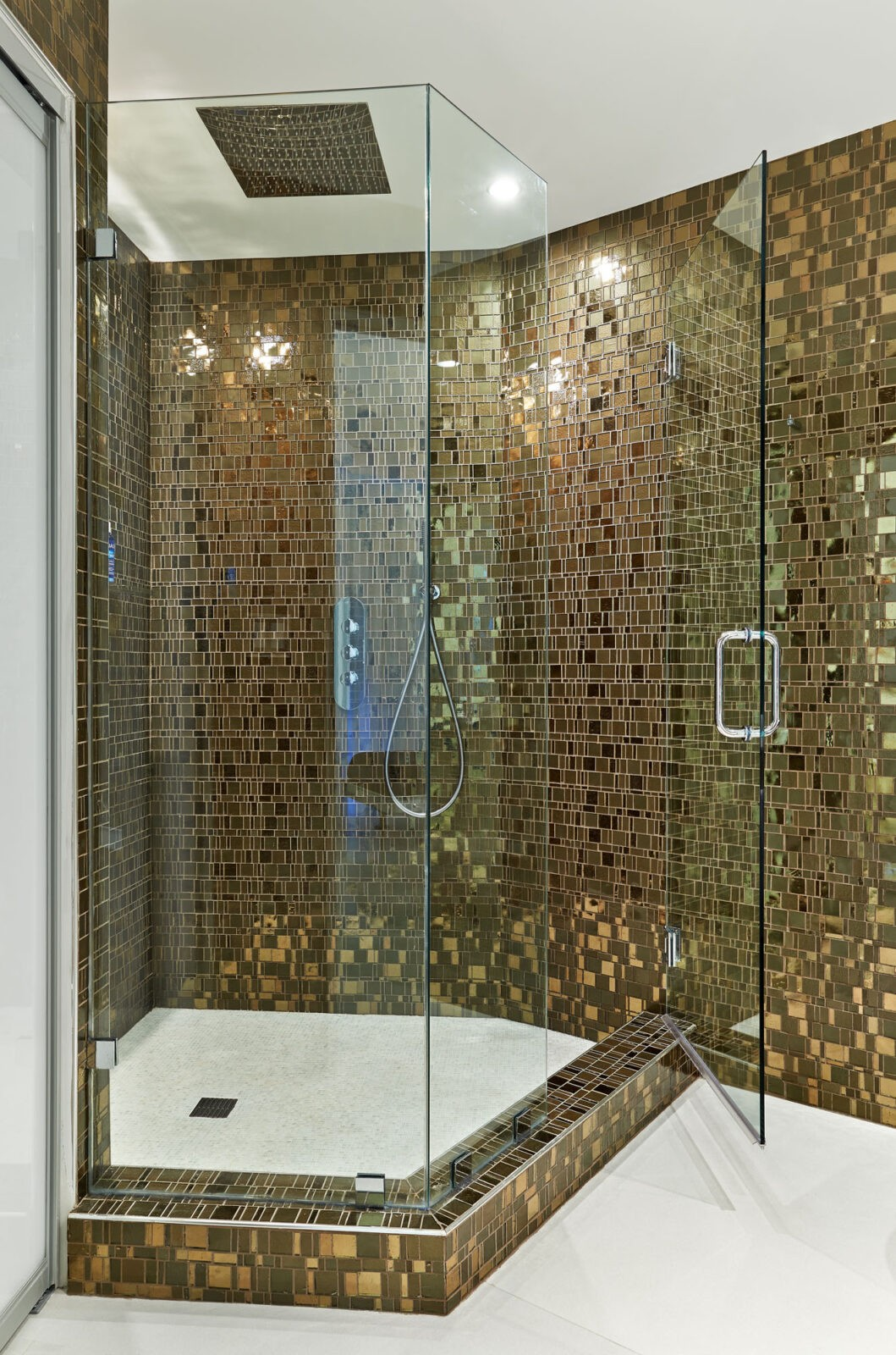 Guest bathroom shower walls are covered in Liberty Bronzite Mosaic Tiles by Granite Transformations