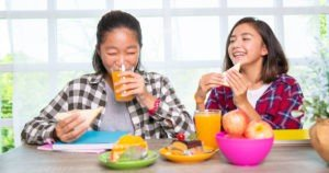 Teenage girls eating breakfast