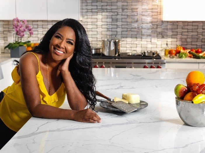Kenya Moore enjoying her newly renovated kitchen by TREND Transformations/Granite Transformations