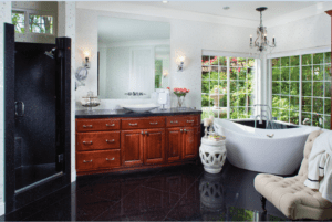 Homeowners are opting for a darker, more dramatic look in the bathroom by using black glass tile.