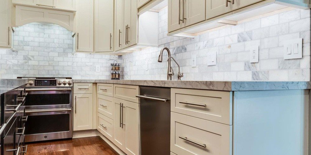 contemporary kitchen with white cabinets and marble countertops