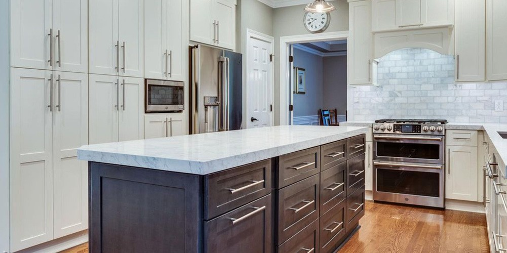 white cabinets with brown cabinet island in contemporary kitchen