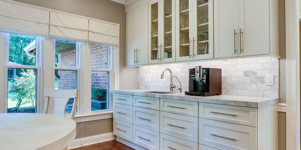kitchen bar with white cabinets and marble countertops
