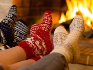 Feet with socks in front of fire place