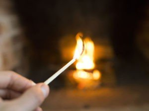 Lit match in front of fireplace