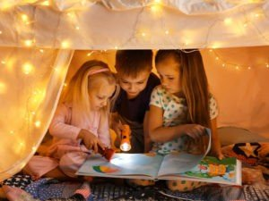 GT Children reading book with flashlight in tent