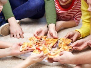 GT Hands of kids eating pizza on the floor