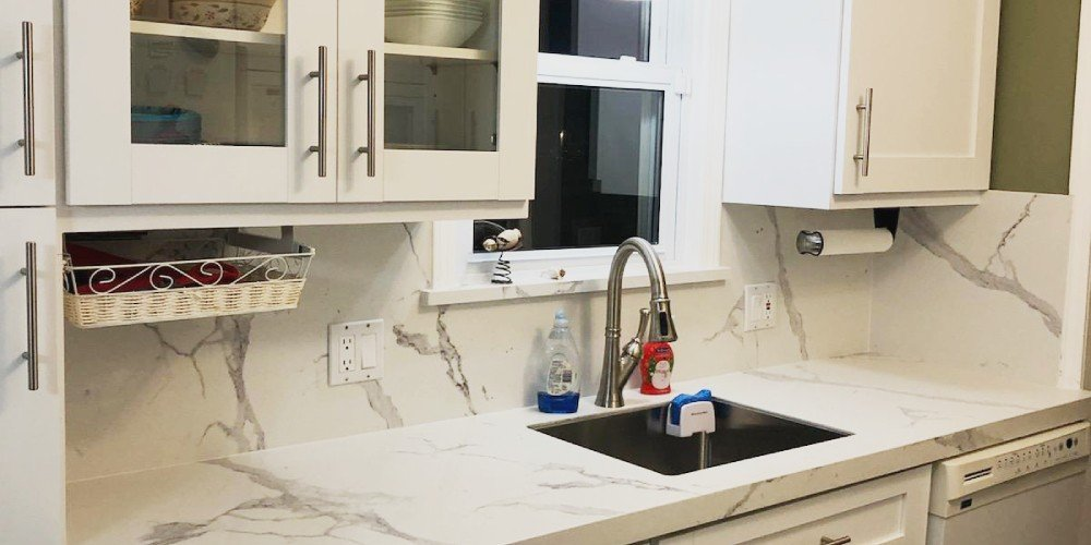 Kitchen remodel featuring white cabinets and marble countertops