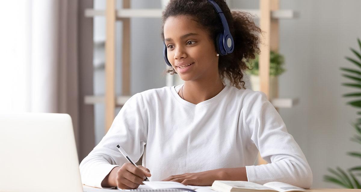 Girl sitting at laptop doing homework