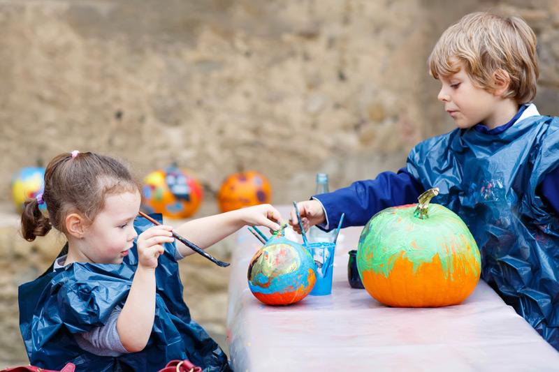 2 children painting pumpkins