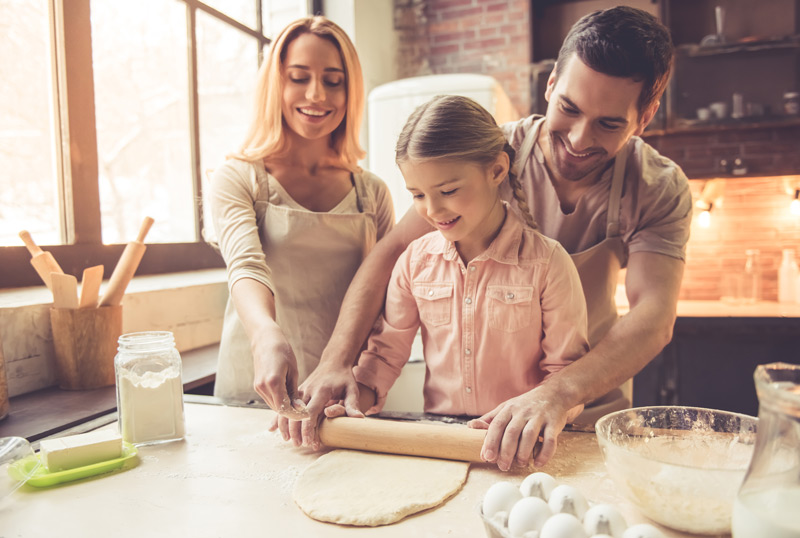 Parents and daughter rolling out dough in the kitchen